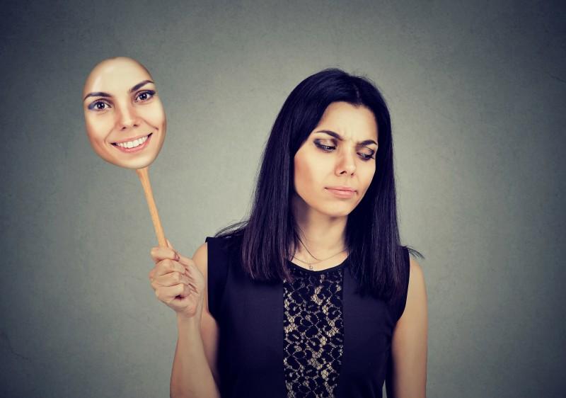 chica triste detrás de una mascara alegre