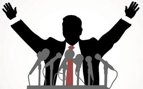 un político con los brazos en alto en un mitin.