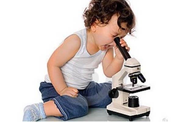 niño mirando en un microscopio